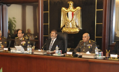 Egyptian President Mohamed Mursi sits next to the head of the Egyptian military General Abdel Fattah al-Sisi and top military and police chiefs during their meeting in Cairo