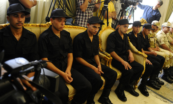 Soldiers who were kidnapped last week sit before a news conference by President Mohamed Mursi after their release
