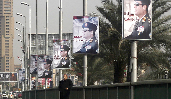 A man stands on a bridge where huge posters of Egypt's army chief Field Marshal Abdel Fattah al-Sisi are hanged in center Cairo