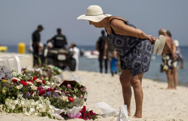 A tourist reads messages left at a makeshift memorial at the beach near the Imperial Marhaba resort, which was attacked by a gunman in Sousse, Tunisia, June 29, 2015. REUTERS/Zohra Bensemra
