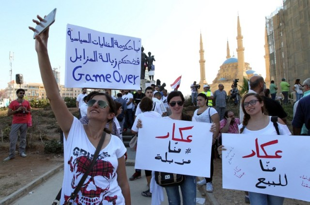 "Lebanese young women take pictures as they hold placards before the start of an anti-government protest organised by a civil society frustrated with a political class they see as corrupt and incapable of providing basic services on August 29, 2015 at Beirut's iconic Martyrs Square. ""Today, we're expecting more than 50,000 protesters,"" said Assaad Thebian of the ""You Stink"" which is stressing the non-partisan nature of the demonstration. The placards read ""Akkar is not for sale (C and R) and ""Game over you government of political trash""(L). AFP PHOTO / ANWAR AMRO"